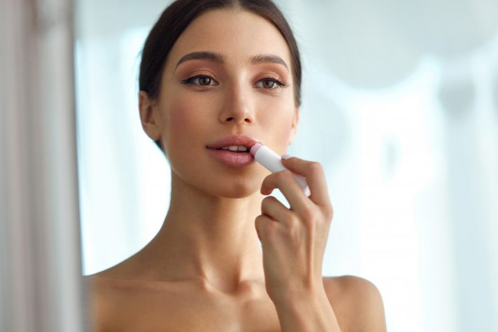 Lips Protection. Beautiful Woman With Beauty Face, Full Lips Applying Lip Balm, Lipcare Stick On. Portrait Of Female Model With Natural Makeup. Lips Skin Care Cosmetics Concept. High Resolution