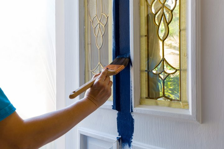 Female hand holding Brush painting house front door with blue paint at home do it yourself project