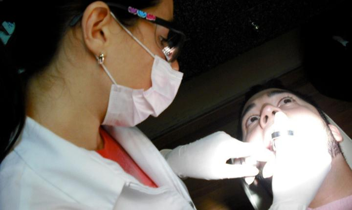 Medical Professional Examining a Patient's Mouth