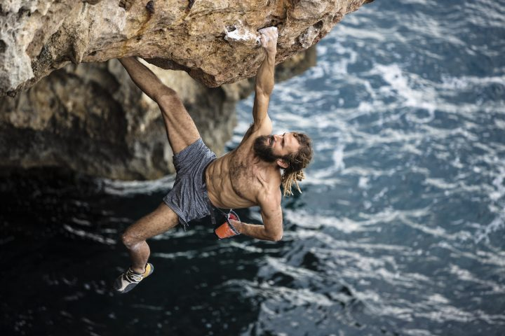 Man practicing deep water soloing rock climbing in Menorca Spain