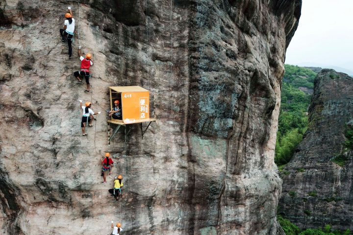 This photo taken on April 25, 2018 shows people rock climbing past a 100-meter-high convenience store on a cliff in Pingjiang in China's central Hunan province. - The store was opened to offer food and water for rock climbers. (Photo by - / AFP) / China OUT (Photo credit should read -/AFP via Getty Images)