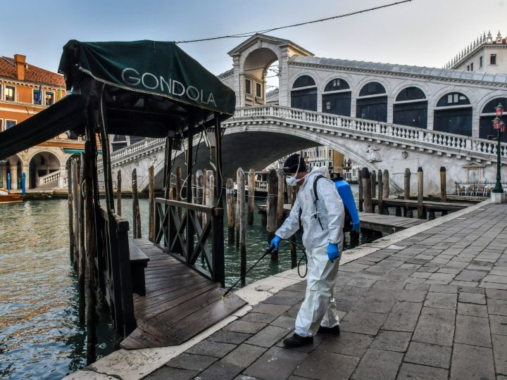 An employee of the municipal company Veritas sprays disinfectant in public areas at the Rialto Bridge in Venice on March 11, 2020, as part of precautionary measures against the spread of the new coronavirus COVID-19, a day after Italy imposed unprecedented national restrictions on its 60 million people Tuesday to control the deadly COVID-19 coronavirus.