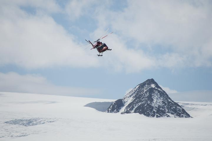 Helicopter flying by mountain