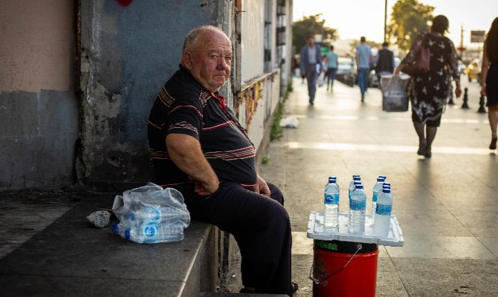 Man selling water on the side of the road