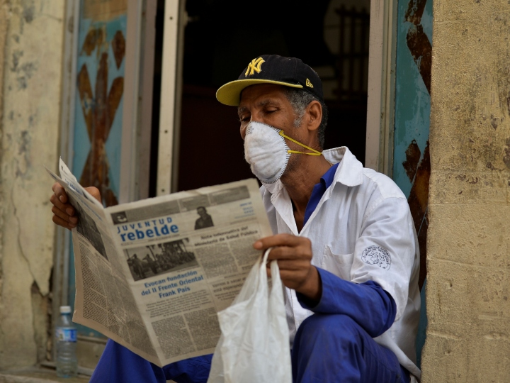 A man reads a newspaper as he wears a face mask in Havana, on March 12, 2020 as the world battles the outbreak of the new coronavirus, COVID-19. - Cuba registered its first three cases on Wednesday. Three Italian tourists, who had arrived Monday in Havana, all tested positive for the virus and have been quarantined.