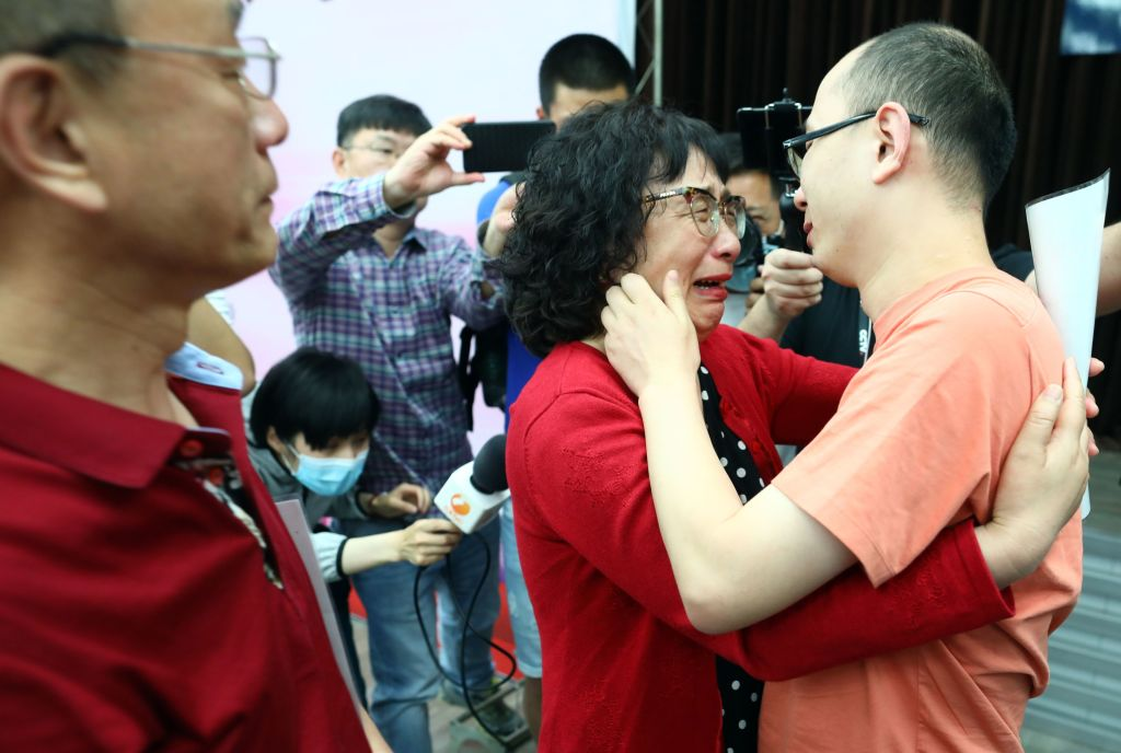 This photo taken on May 18, 2020 shows Mao Yin (R) reuniting with his mother Li Jingzhi (C) and father Mao Zhenping (L) in Xian, in China's northern Shaanxi province. - A Chinese man who was kidnapped as a toddler 32 years ago has been reunited with his biological parents, after police used facial recognition technology to track him down. (Photo by STR / AFP) / China OUT